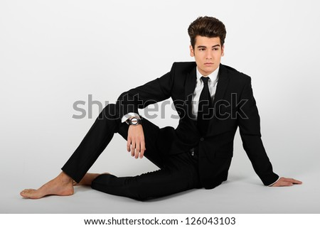 Portrait of a young businessman wearing a suit, barefoot, isolated on white background - stock photo