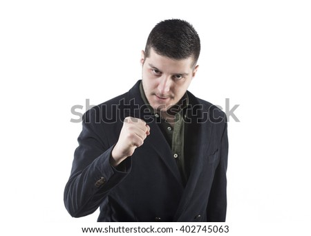 portrait of a young businessman with a fist looking serious and determined on a white background - stock photo