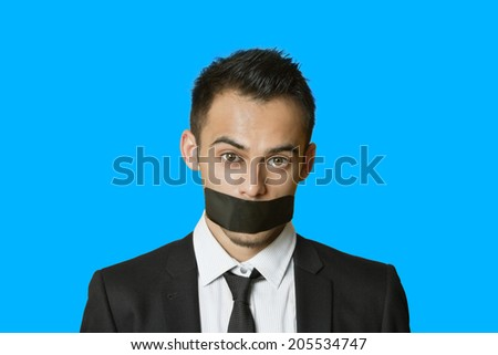 Portrait of a young businessman with adhesive tape on mouth over colored background - stock photo