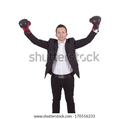 Portrait of a young businessman with boxing gloves raising his arms after victory - stock photo