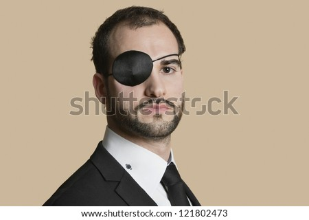 Portrait of a young businessman with eye patch over colored background - stock photo
