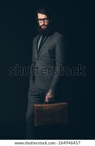 Portrait of a Young Businessman with Long Goatee, Wearing Elegant Formal Wear With Eyeglasses, Holding his Briefcase and Looking at the Camera. Isolated on Black Background. - stock photo