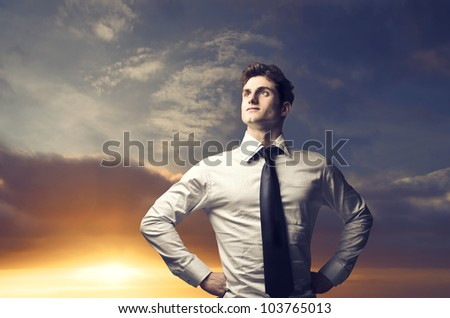 Portrait of a young businessman with sunrise in the background - stock photo