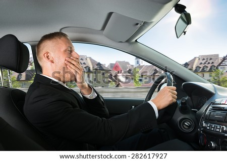 Portrait Of A Young Businessman Yawning While Driving Car - stock photo