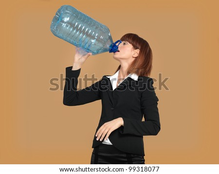 portrait of a young businesswoman, drinking water from a big bottle, on beige background - stock photo