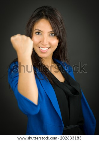 Portrait of a young businesswoman showing fist and celebrating her success - stock photo