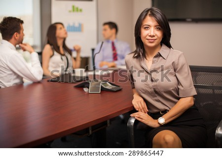 Portrait of a young businesswoman sitting in a conference room with some of her colleagues - stock photo