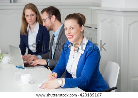Portrait of a young businesswoman taking notes during the meeting   - stock photo