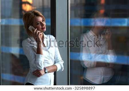 Portrait of a young businesswoman talking on cellphone while standing by her office window in modern skyscraper building, female entrepreneur having mobile phone conversation with copy space for text - stock photo