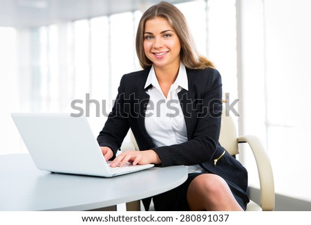 Portrait of a young businesswoman using laptop at office - stock photo