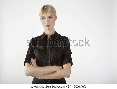 Portrait of a young businesswoman with arms crossed on gray background - stock photo
