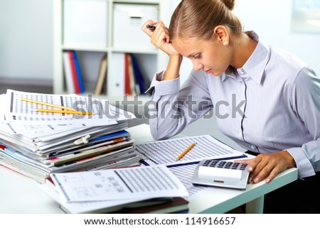 Portrait of a young businesswoman working with papers in office - stock photo