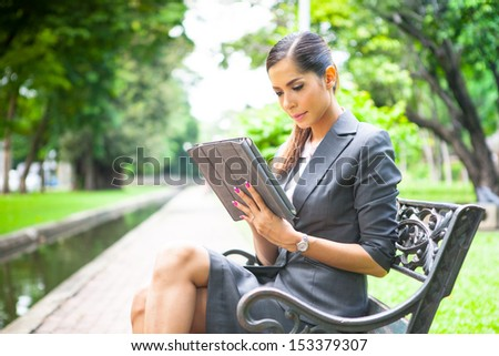 Portrait of a young businesswoman working with tablet at the park. - stock photo