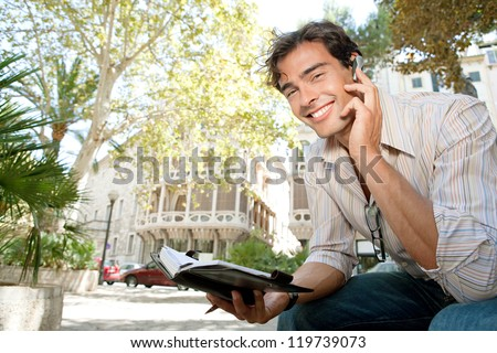 Portrait of a young casual businessman using a hands free ear device to have a conversation while sitting outdoors near classic buildings in the city. - stock photo