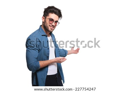 Portrait of a young casual man presenting something to his left, isolated - stock photo