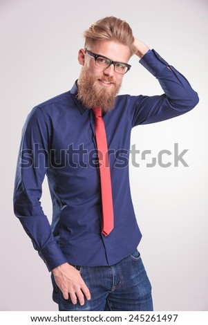 Portrait of a young casual man smiling at the camera while fixing his hair. He is also holding a thumb in his pocket. - stock photo