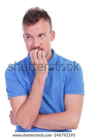 portrait of a young casual man thinking while biting his nails and looking away. isolated on a white background - stock photo