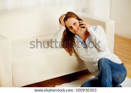 Portrait of a young casual woman having fun on cell phone at home - stock photo