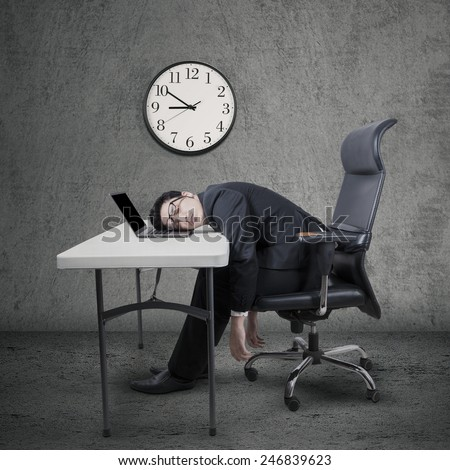 Portrait of a young caucasian businessman works overtime and sleep at desk - stock photo