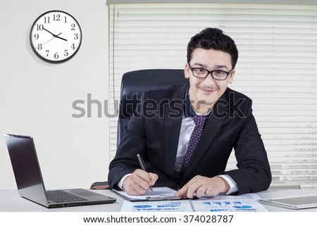 Portrait of a young caucasian entrepreneur working in the office and smiling at the camera with a clock on the wall - stock photo