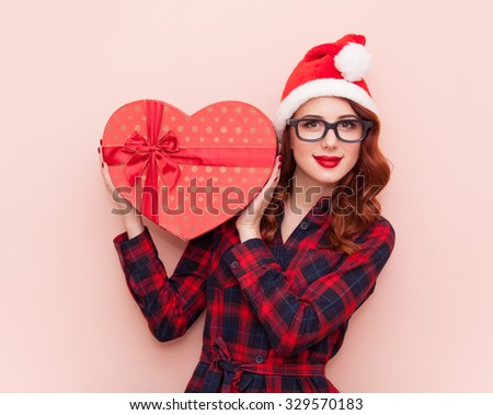 Portrait of a young caucasian girl with gift box on pink background. - stock photo