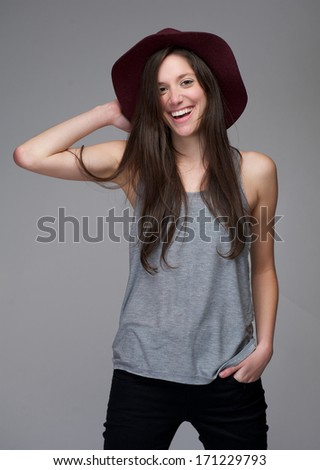 Portrait of a young caucasian woman laughing with red hat on gray background - stock photo
