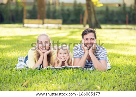 Portrait of a young cheerful family lying on the grass and posing at camera - stock photo