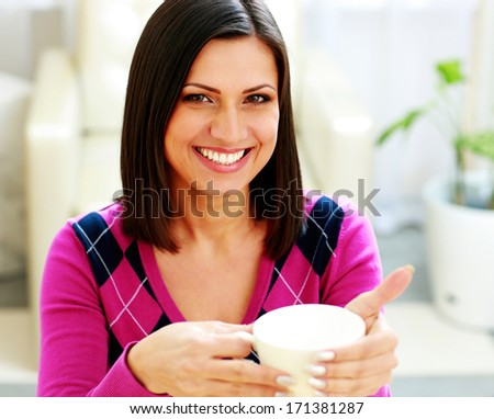 Portrait of a young cheerful woman holding cup of coffee - stock photo