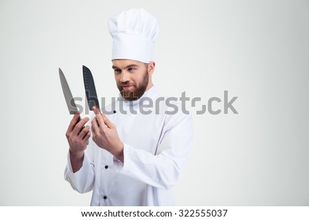 Portrait of a young chef cook holding and looking on knifes isolated on a white background - stock photo