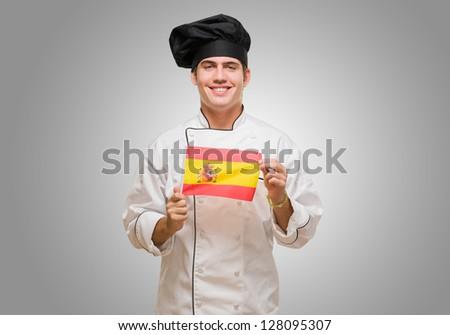 Portrait Of A Young Chef Holding Spanish Flag against a grey background - stock photo