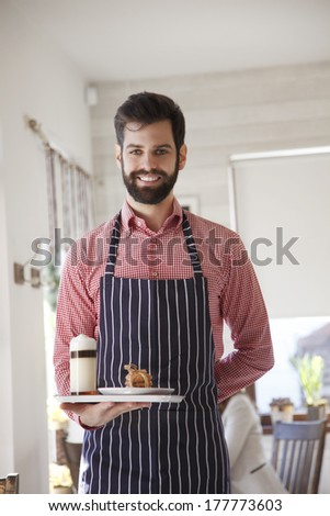 Portrait of a young coffee shop owner holding tray in his hand.  - stock photo