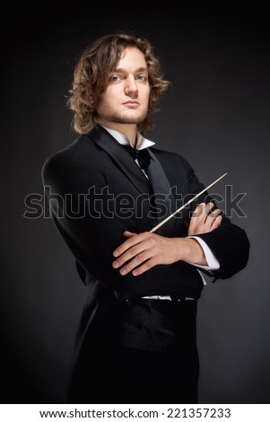 Portrait of a Young Conductor Holding a  Baton. - stock photo