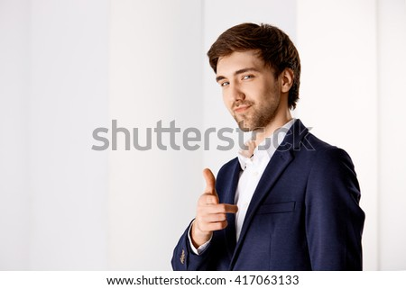 Portrait of a young confident businessman looking at camera smiling showing thumb up. - stock photo