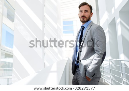 Portrait of a young confident man office worker dressed in luxury corporate clothes standing in modern interior, handsome successful male managing director resting after business meeting with partners  - stock photo