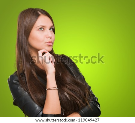 Portrait Of A Young Confused Woman against a green background - stock photo