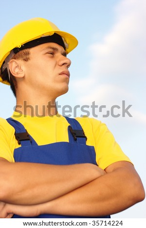 Portrait of a young construction worker, dressed in blue-and-yellow uniform and hard hat, over blue sky - stock photo