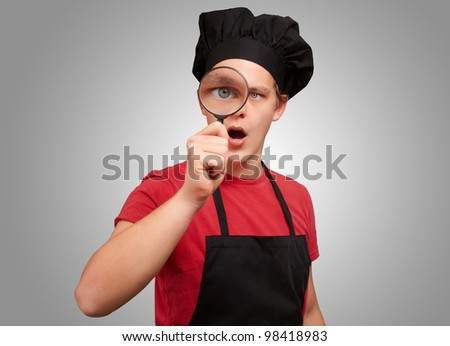 portrait of a young cook holding a magnifying glass against a grey background - stock photo