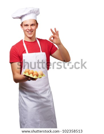 portrait of a young cook man holding an egg box and doing a good gesture over a white background - stock photo