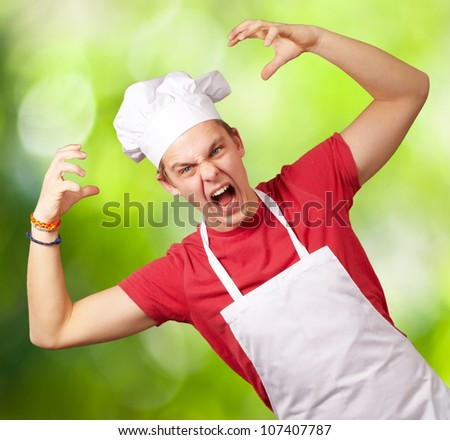 portrait of a young cook man wearing an apron doing an aggressive gesture against a nature background - stock photo