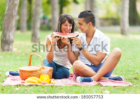 Portrait of a young couple eating watermelon at a picnic - stock photo