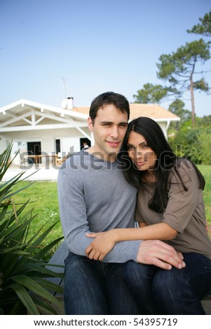 Portrait of a young couple in front of a house - stock photo
