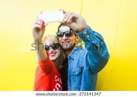 portrait of a young couple in love on the background of yellow wall, young blond woman with red manicure and  lips in sunglasses and a red sweatshirt and attractive guy with a beard, a  jacket and cap - stock photo