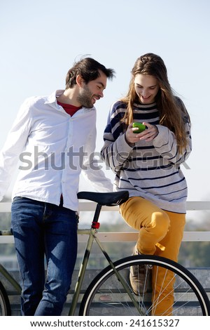 Portrait of a young couple looking at mobile phone outdoors  - stock photo