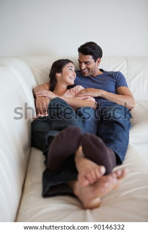 Portrait of a young couple lying on a sofa while looking at each other - stock photo