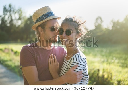 Portrait of a young couple on a country road on a summer evening - stock photo