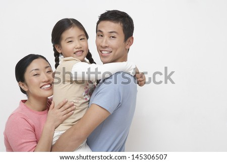 Portrait of a young couple with daughter against white background - stock photo