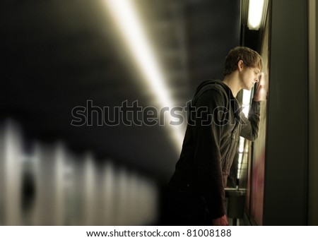 Portrait of a young depressed man in subway station - stock photo