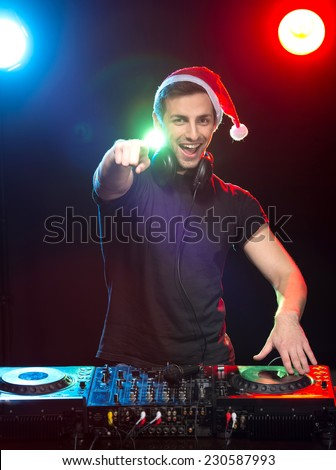 Portrait of a young DJ at work with a mixer, the club lights on the background. - stock photo