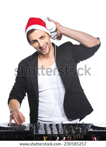 Portrait of a young DJ standing at the mixer in christmas hat on a light background. - stock photo