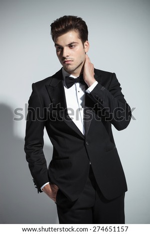 Portrait of a young elegant business man holding his hand to his neck while looking away from the camera. - stock photo
